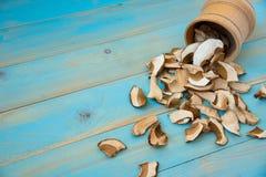 Champignons secs de porcini sur le fond en bois bleu photographie stock libre de droits