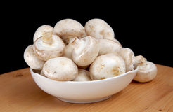 Champignons in a white bowl Stock Photos