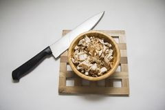 champignons in wooden bowl with large knife Royalty Free Stock Photography