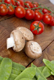 Champinjoner, ärtor och tomater Arkivfoton