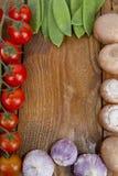 Champinjoner, ärtor, vitlök och tomater Arkivbild