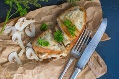 Champinjoner och ostsmörgås, bästa sikt med den selektiva fokusen Royaltyfri Bild