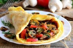 Champinjoner och tomatomelettidé Hem- omelett som är välfylld med champinjoner, tomater och dill på en platta och tappningen trät Royaltyfria Bilder