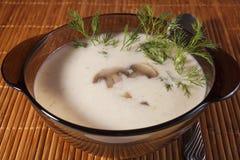 Champinjoner, potatisar och kräm- soup för ost i ett exponeringsglas pläterar Arkivfoto