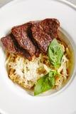 ChampinjonRisotto med grillade skivor av nötkött i den vita plattaöverkanten arkivbilder