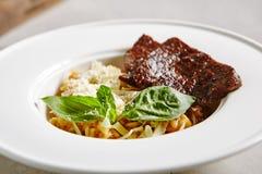 ChampinjonRisotto med grillade skivor av nötkött i den vita plattan arkivbild
