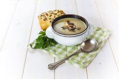 Champinjonsoppa med en brödrulle och persilja Royaltyfria Bilder