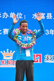 Champion athlete. The champion athlete on the podium waving to the audience.Half international marathon in fushui county in yunnan province in China, time: on Stock Photo