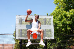 Champion basketball player sitting in hoop Stock Photography