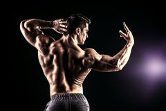 Champion. Beautiful muscular man bodybuilder posing back over dark background Stock Images