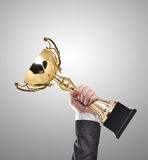 Champion. Businessman holding a champion golden trophy royalty free stock images