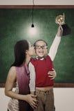 Champion d'école tenant le baiser de trophée par la maman dans la classe Image libre de droits