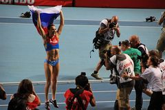 Champion E. Isinbayeva jumping with Russian flag Royalty Free Stock Images