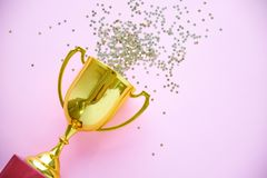 Champion gold cup trophy on a pink background. minimalism style, victory celebration concept. and golden stars of. Champion gold cup trophy on yellow background stock image