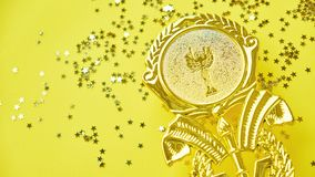 Champion gold cup trophy on yellow background. minimalism style, victory celebration concept. and golden stars of. Champion gold cup trophy on yellow background stock photo