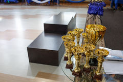 Champion golden trophies. Cup for the first place. Pedestal on the background.  royalty free stock photo