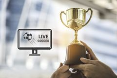 Champion golden trophy for winner background with live soccer sc. Reen icon on right. Success and achievement concept. Sport and cup award theme. Television stock photos