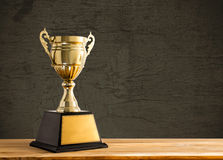 Champion golden trophy on wood table with copy space, copy space. Ready for your design stock photography