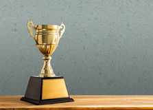 champion golden trophy on wood table with copy space, copy space Royalty Free Stock Photos