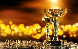 Champion golden trophy on wood table with spot lights on background. Champion golden trophy on wood table with blur spot lights on background. Copyspace for text Stock Photos