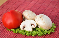 Champion mushroom with tomato. Fresh mushroom with tomato on lettuce leaf red over straw mat stock photography