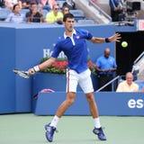 Champion Novak Djokovic de Grand Chelem de neuf fois dans l'action pendant le premier match de rond à l'US Open 2015 Photo libre de droits
