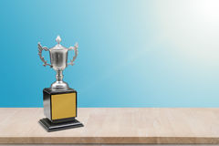 Champion trophy placed on wooden table. Royalty Free Stock Images