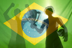 Champion Winning Football Players Brazilian Flag. Shadow silhouettes of football players celebrating holding winning trophy and football against Brazilian flag Stock Images