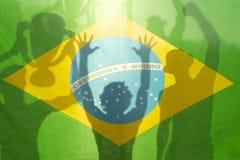 Champion Winning Football Players Brazilian Flag. Brazilian flag football players shadow silhouettes celebrating holding winning trophy against bright sunlight Royalty Free Stock Image