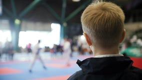 Championnat de karaté - combat de observation de karaté de garçon d'adolescent - spectateur à la concurrence, au ralenti banque de vidéos
