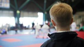 Championnat de karaté - garçon d'adolescent regardant le combat de karaté - spectateur à la concurrence banque de vidéos