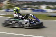 Championnat de Karting Le conducteur dans les karts portant le casque, emballant le costume participent à la course de kart Expos images stock