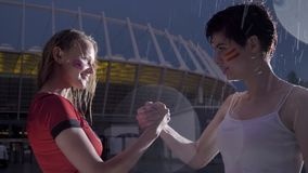 Champions League, two young girls football fans in the rain are shaking hands, confrontation concept 60 fps stock video