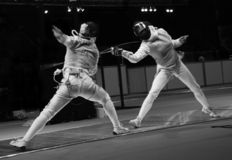 Championship on fencing. Duel two sportsmen on fencing Stock Photos