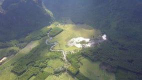Champs avec le marais et la rivière parmi la vue aérienne de montagnes banque de vidéos