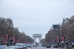 Champs Elysees avenue with the Arc de Triomphe in background during a cloudy foggy polluted day , with a traffic jam in front. Picture of Arc de Triomphe and the Royalty Free Stock Photo