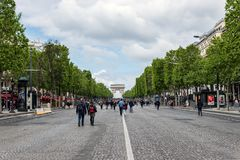 Champs Elysees avenue closed to car traffic - Paris. Paris, France - May 5, 2019: People wandering on Champs Elysees avenue with Arc de triomphe in background royalty free stock images
