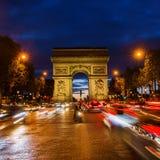 Champs-Elysees et Arc de Triomphe la nuit Photographie stock libre de droits