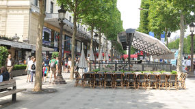 Champs Elysees. Paris, France - July 8, 2015: Groups of tourists walk across the famous Champs Elysees boulevard in central Paris, France Royalty Free Stock Photo
