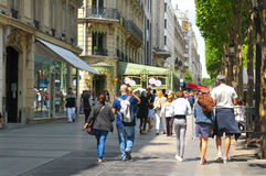 Champs Elysees. Paris, France - July 8, 2015: Groups of tourists walk across the famous Champs Elysees boulevard in central Paris, France Stock Photo
