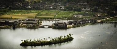 Champs et village chinois par la rivière Photo stock