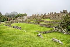 Champs verts d'Inca Citadel antique sous le brouillard lourd Images libres de droits