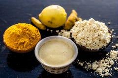 Chana, haldi, pacchetto ubtan o ayurvedic del Ka del vuoto di fronte di curcuma, del limone e della farina di grammo su superfici immagini stock