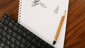 Chancery on a wooden table: a pencil, paperclips, notebook, keyboard. Concept office or school, knowledge day, the first of Septem. Ber. Video footage is stock video footage