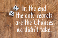 Chances in life quote dice on wood background. Roll of dice on wooden background with inspirational quote In the end the only regrets are the Chances we didn't Royalty Free Stock Photos