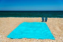 Chancleta azul y toalla de la sandalia en la arena amarilla Tiempo y accesorios en la playa, vacaciones de la diversión del veran Fotografía de archivo