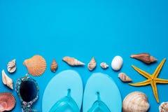 Chancletas; conchas marinas en fondo azul copie el espacio para su texto Imagen de archivo libre de regalías