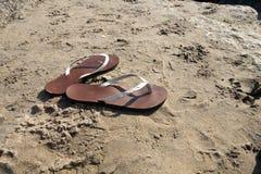 Chancletas de las sandalias de la mujer en la playa arenosa imagen de archivo