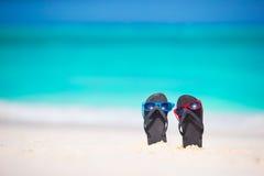 Chancletas del verano con las gafas de sol en la playa blanca Imagen de archivo