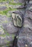 Chancletas desechadas en una roca de la playa Imagen de archivo